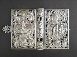 silver book cover with biblical images