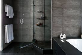 luxurious in ground bath with walk in shower and glass shower screen also wall shelves plus grey concrete wall