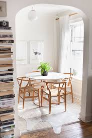 modern all white dining e with cowhide rug wood chairs and stacked books