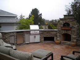 smoker large outdoor kitchen with a connected stone fireplace and pizza oven