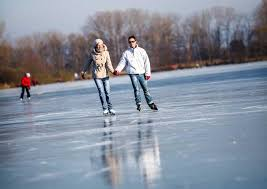winter outdoor activities.  Winter A Man And Woman Skat On Reflective Ice In The Distant Left Is A Younger To Winter Outdoor Activities