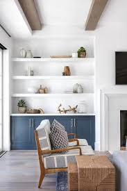 white floating shelves over blue built in cabinets display fine pottery and decor in a cottage living room beside a white beveled fireplace