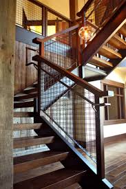 architectural woven wire mesh infill on this staircase maintains the  uninterrupted sight lines in this home.