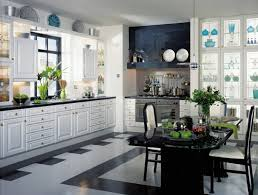 black and white kitchen tile flooring under black countertop and black large dining table also two small chairs under tiny pendant lamp near outsize white