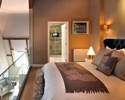 warm bedroom design. Example Of A Mid-sized Trendy Loft-style Medium Tone Wood Floor Bedroom Design Warm