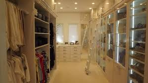 modern white walk in closet design with ceiling lamps as well as
