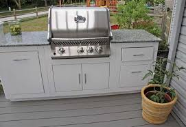 an outdoor kitchen set on a deck featuring a small bar with a granite countertop