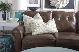 brown leather sofa featuring fine olive green fl patterned decorative pillows