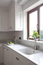 all white kitchen with tiles and quartz counters