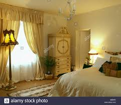 pale yellow bedroom.  Yellow White Voile And Yellow Silk Curtains On Window In Pale Bedroom With  Lighted Standard Lamp Cream Cupboard Throughout Pale Yellow Bedroom M