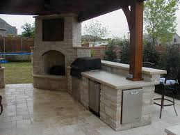 awesome outdoor fireplace with covered tv connects to outdoor kitchen love the design and stonework