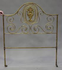 a 20th century french gilded wrought metal single bed each end with a scrollwork frame centred by a