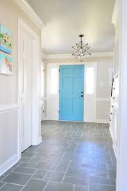 slate tile floor foyer with clean white grout and colorful blue door