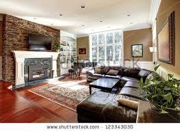 living room with stone fireplace. luxury living room with stone fireplace and leather sofas, cherry hardwood nice rug. e