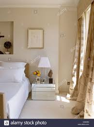 next mirrored furniture. White Lamp On Mirrored Bedside Table Next To Double Bed In Contemporary Bedroom With Opulent Cream Silk Curtains The Window Furniture