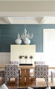 Elegant transitional dining room with peacock blue grasscloth wallpaper  paired with board and batten walls.