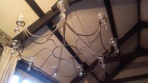 ornate wrought iron chandelier with glass cups for holding candles tealights