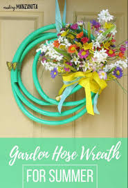 bright green garden hose upcycled into a summer wreath with flowers and text overlay that says