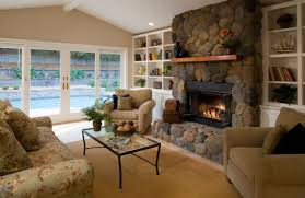 living room with stone fireplace. well ventilated living room with a stone fireplace that sports daft glass doors