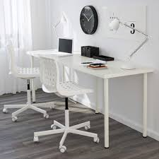 clean white ikea linnmon adils desk setup with laptop on it