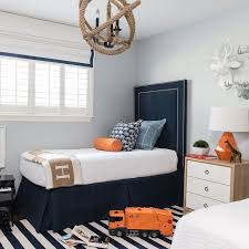Blue and orange kid's room boasts pale blue walls lined with tall navy blue  velvet headboards