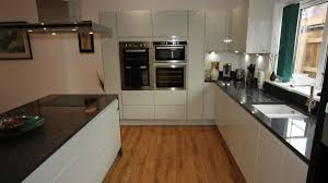 contemporary glossy white kitchen cupboards with black granite worktops