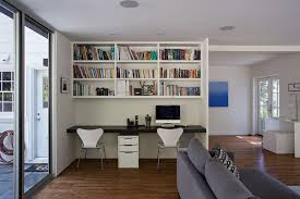 office built in. a black desk built-in below the white shelves makes this small space functional home office for two. built in