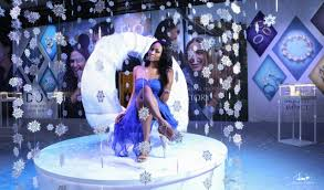 a young beautiful black model in a blue purple dress sitting down upon a white
