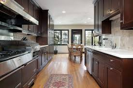 dark wood kitchen cabinets. This Parallel Kitchen Layout Uses The Light To Prevent Narrow And Dark Room From Becoming Wood Cabinets