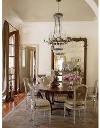 gorgeous dining room w french style dan marty see more antique gilt floor mirror crystal and metal chandelier french cane back cushioned chairs