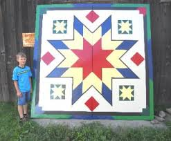 flying geese barn quilt block being installed onto a customer s barn sho fly block painted on barn door