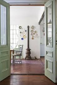 green painted doors leading to room with pot bellied stove casa chaucha