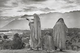 four robed figures in foreground on a plateau overlooking a village water and mounns in
