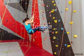 happy sporty woman with climbing equipment hanging on a rope at indoor rock climbing artificial on rock climbing artificial wall with happy sporty woman with climbing equipment hanging on a rope at