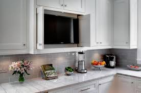 black tv in the white kitchen cabinets along with marble countertop and gray ceramic backsplash design