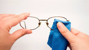 cleaning glasses with a microfiber cloth and cleaner
