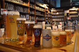 a selection of beers in diffe sized beer glasses on a bar top