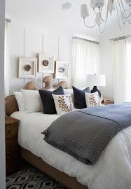 stunning bedroom with reed eight light chandelier hung from vaulted ceilings over a noir burlap bed dressed with crinkled white bedding layered with a gray
