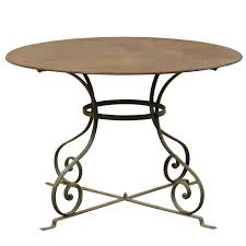 french mid 20th century round patio dining table with scrolled legs and patina for