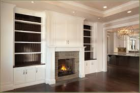 built in cabinets living room around fireplace with white marble countertop under recessed lamps and chandelier