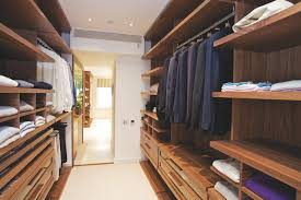 Contemporary men's walk-in closet idea in London with open cabinets and  medium tone wood