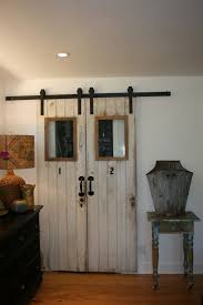 shabby white wooden barn door with black handler also double glass windows on the top with brown wooden frame