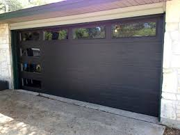 dark garage door metal door glass window stone wall driveway