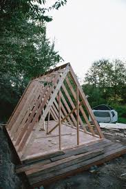 It helps to nail up supports to hold them as well until the actual plywood  roof goes on. This is the bones of what will start to look like an A-frame.