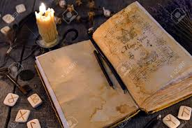 open old book with magic spells runes candle and key on witch table