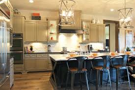 burrows cabinets kitchen with black island and gray wall cabinets wood vent hood and modern