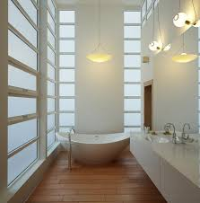 in this bathroom two types of pendant lights work together ball like glass pendants hang above the vanity while a bowl shape glass pendant mimics the tub