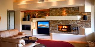 custom drywall entertainment center with stacked stone walls decorative lighted display shelves and fireplace