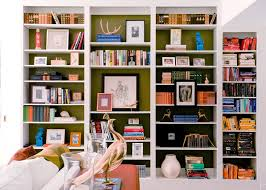 the back of this shelf is painted a contrasting avocado green shelves feature books framed art and small decorative items above