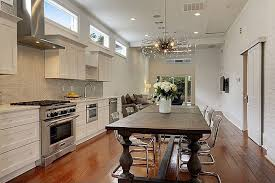 contemporary one wall kitchen with white cabinets wood floors and wood dining table
